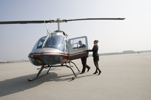 Woman assisting a businessman board a helicopter - FSIF02414
