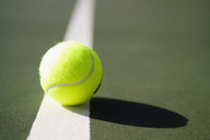 A tennis ball sitting on a white line - FSIF02417