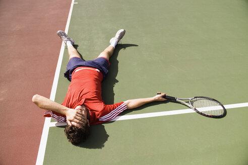 A tennis player lying down on the tennis court - FSIF02420