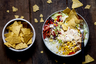 Taco salad bowl with rice, corn, chili con carne, kidney beans, iceberg lettuce, sour cream, nacho chips, tomatoes - SBDF03465