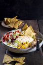 Taco salad bowl with rice, corn, chili con carne, kidney beans, iceberg lettuce, sour cream, nacho chips, tomatoes - SBDF03468