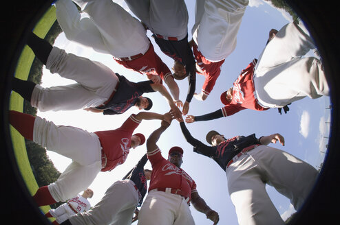 A baseball team with their hands stacked together in a huddle - FSIF02493