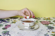 A woman's hand dropping a heart shaped sugar cube into a cup of tea - FSIF02496