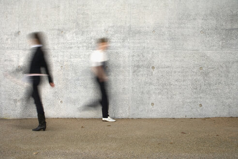 Two people walking past a wall - FSIF02511