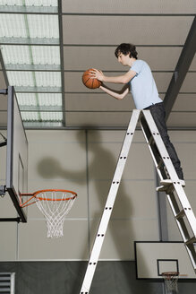 A Young Man standing on a ladder preparing to drop a basketball into a basketball hoop - FSIF02517