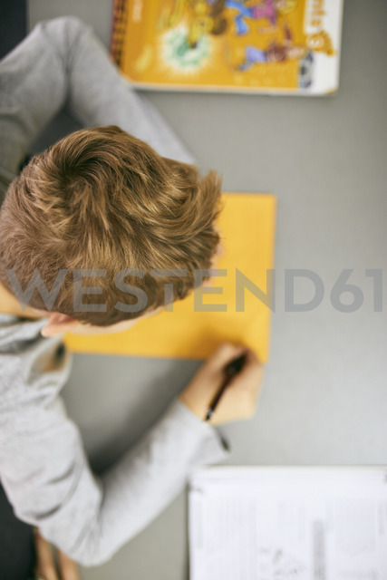 Schoolboy writing on desk in class - ZEDF01190