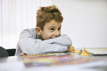 Grinning schoolboy leaning on desk in class - ZEDF01196