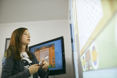 Schoolgirl in class looking at interactive whiteboard - ZEDF01202