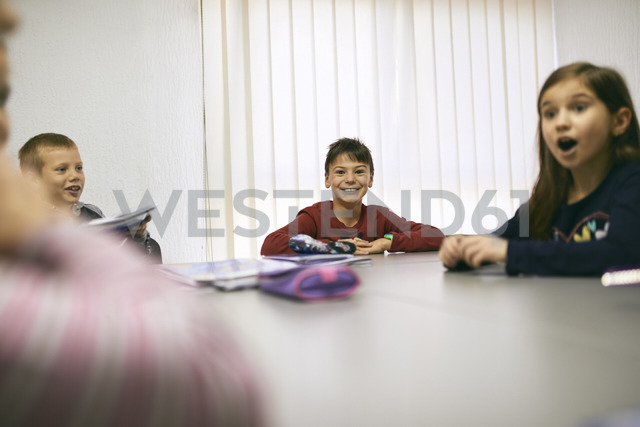 Happy students in class sitting at table - ZEDF01208