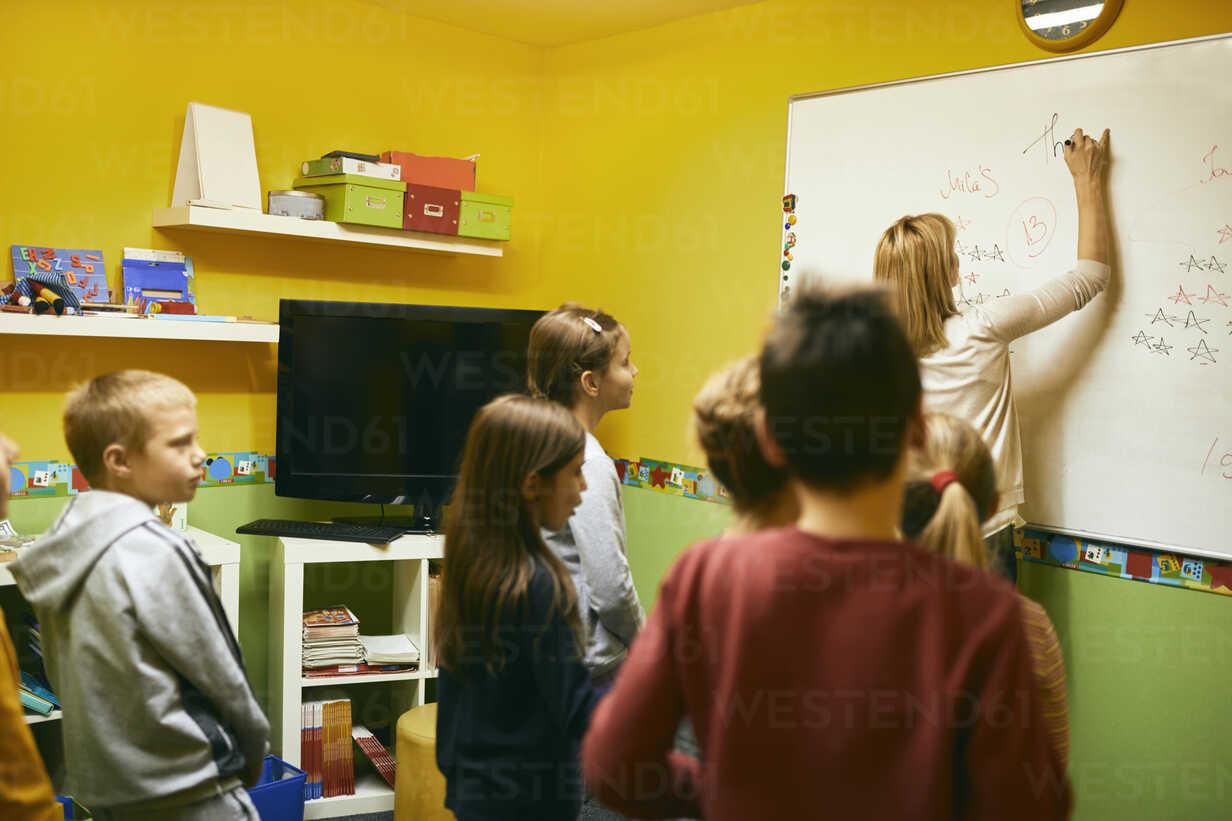 Teacher with students writing on whiteboard - ZEDF01226 - Zeljko Dangubic/Westend61