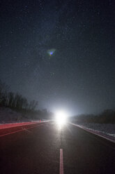 Russia, Amur Oblast, empty country road under starry sky in winter - VPIF00320
