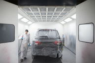 Auto painter painting a car inside a paint booth - RAEF01981