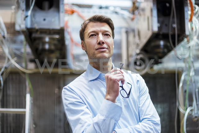 Portrait of confident businessman in factory - DIGF03410