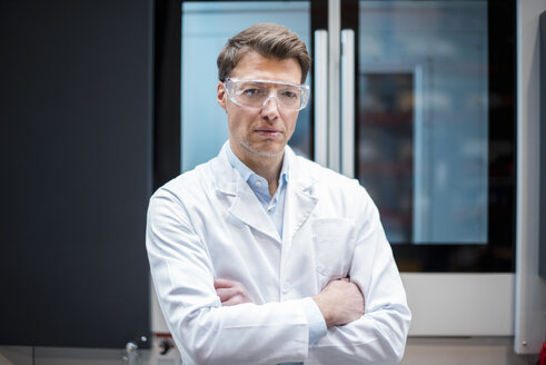 Portrait of man wearing lab coat and safety goggles at machine - DIGF03413