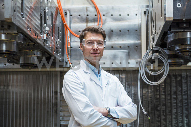 Portrait of man wearing lab coat and safety goggles at machine - DIGF03416