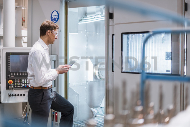 Businessman at machine in factory wearing safety goggles holding laptop - DIGF03419