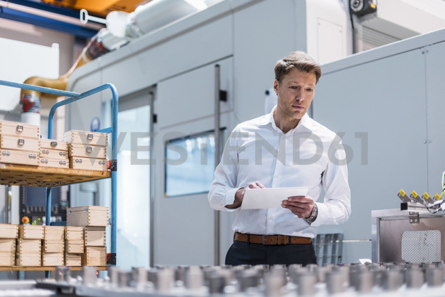 Businessman in factory holding tablet looking at machine - DIGF03422