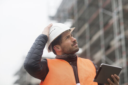 Man with tablet wearing safety vest and hard hat at construction site - SGF02192