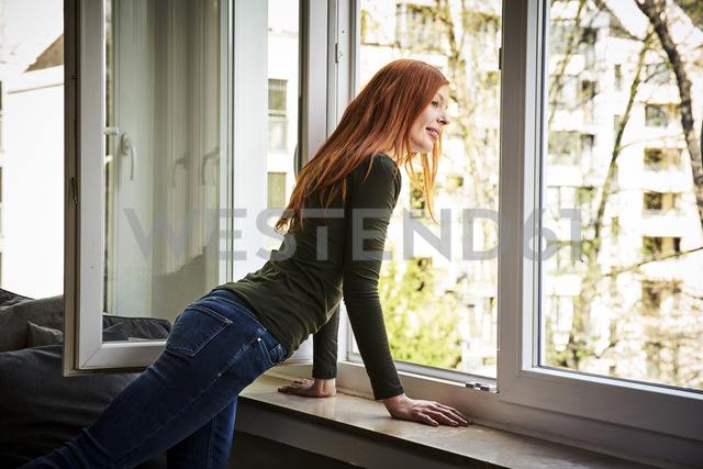 Redheaded woman looking out of window - FMKF04862