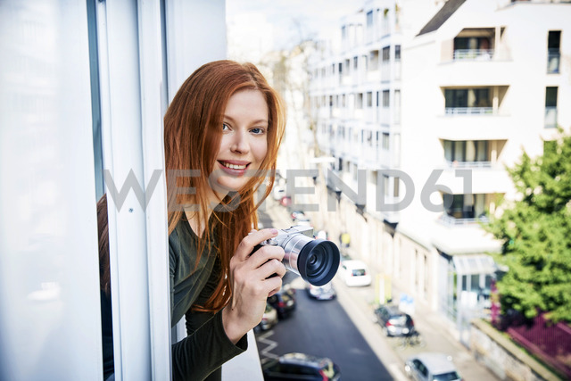 Portrait of smiling redheaded woman with camera leaning out of window - FMKF04865