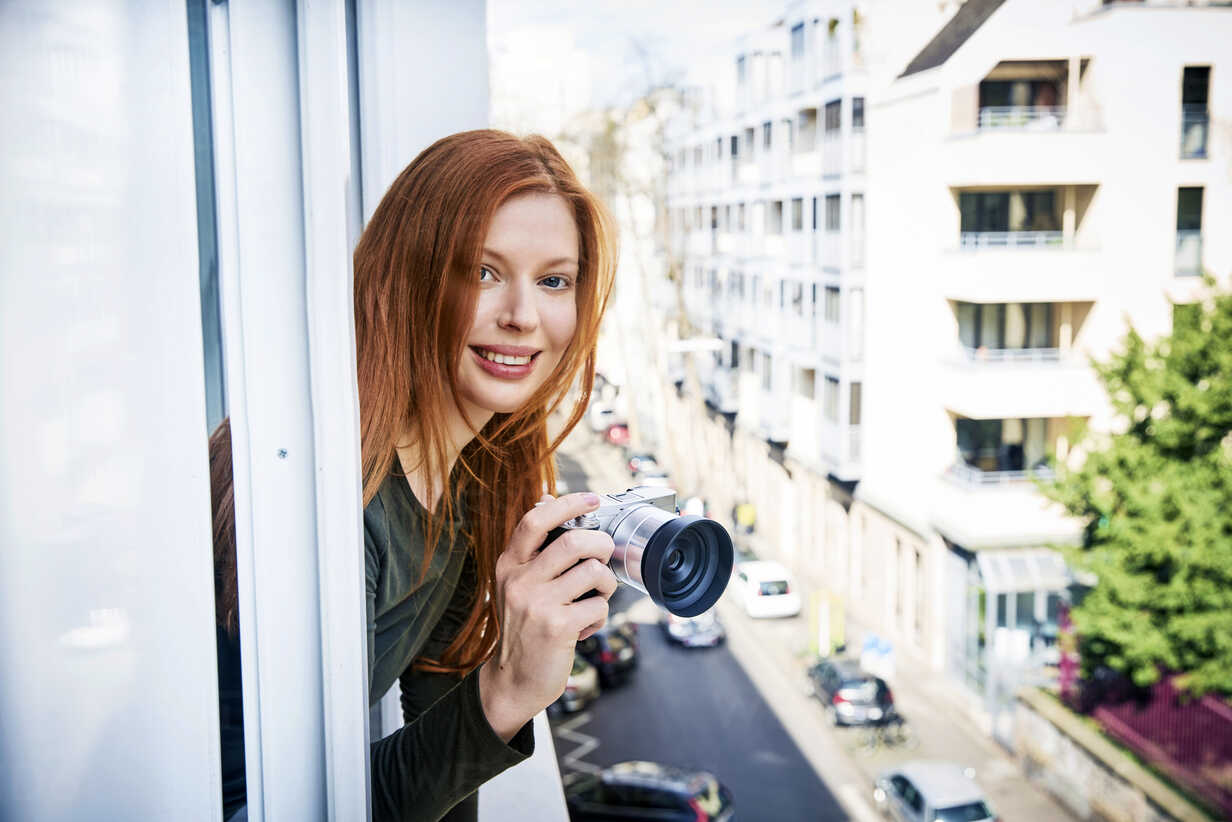 Portrait of smiling redheaded woman with camera leaning out of window - FMKF04865 - Jo Kirchherr/Westend61