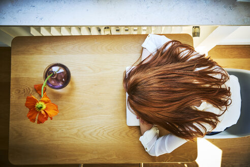 Redheaded woman resting at table with laptop, top view - FMKF04871