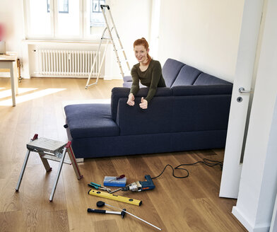 Redheaded woman with tools in the living room - FMKF04874