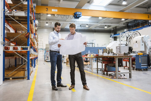 Two men in factory looking at plan - DIGF03430