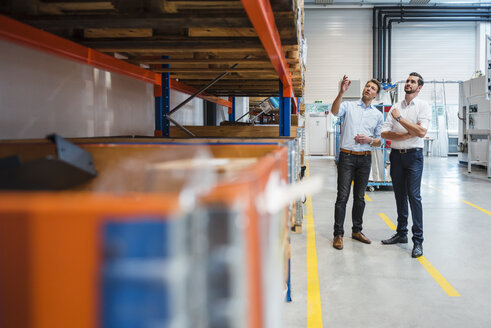 Two men talking in factory storeroom - DIGF03445