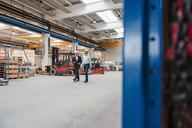 Two men wearing hard hats walking and talking in factory shop floor - DIGF03448