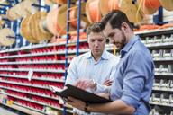 Two men with folder talking in factory storeroom - DIGF03460