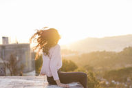 Young woman sitting on a wall at sunset tossing her hair - AFVF00119
