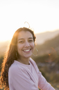 Portrait of laughing young woman with long hair at sunset - AFVF00122