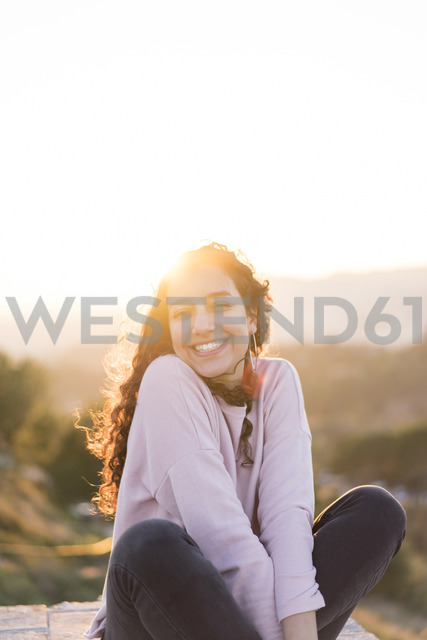 Portrait of happy young woman with long hair sitting on a wall at sunset - AFVF00125