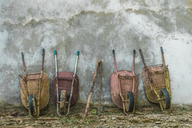 Four old wheelbarrows leaning against wall - AFVF00131