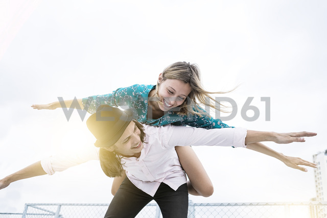 Young affectionate couple having fun together on rooftop, pretending to fly - SBOF01357