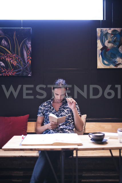 Artist sitting in cafe and reading in small notebook - SBOF01360