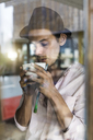 Artist taking a break from his work,  leaning agains window, drinking coffee - SBOF01363
