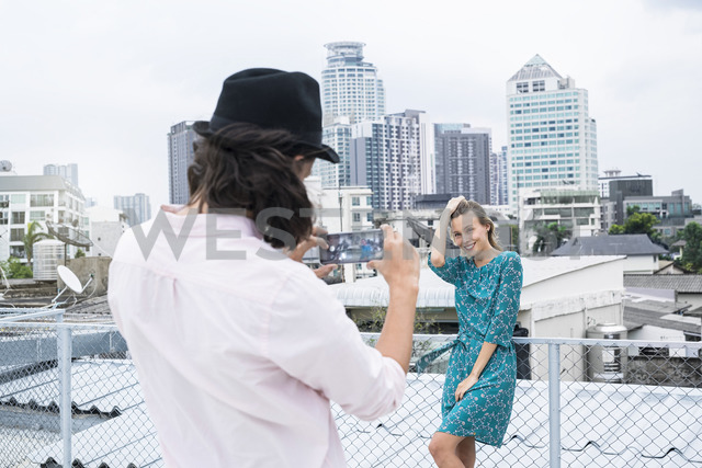 TYoung man with smartphone taking picture of girlfriend posing on rooftop - SBOF01378