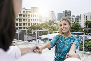 Young woman holding hands with boyfriend on rooftop - SBOF01381
