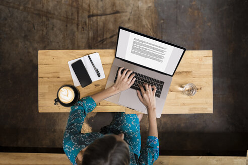 Young woman with green dress sitting in cafe , working on her laptop - SBOF01396