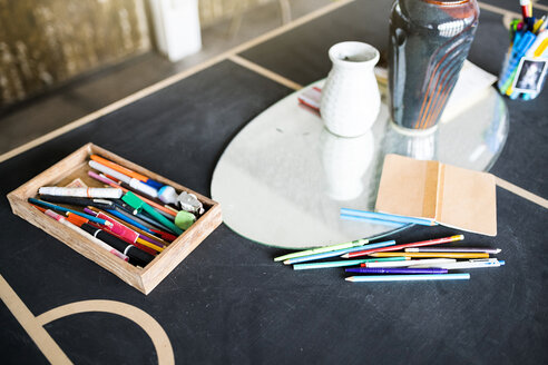 Crayons, pens and a notebook on a table in artist's studio - SBOF01411