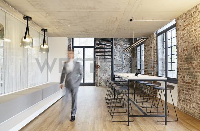 Businessman walking in modern office - PDF01444