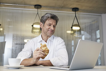 Businessman using laptop while eating croissant - PDF01447