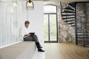 Businessman sitting on bench in modern office using tablet - PDF01450