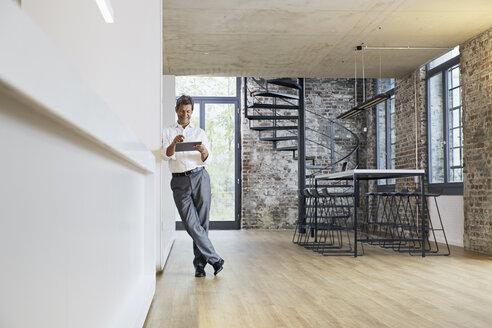 Businessman in modern office using tablet - PDF01456