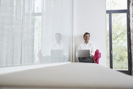 Laughing businessman with pink socks using laptop in office - PDF01459