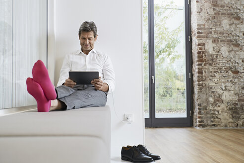 Businessman with pink socks using tablet in office - PDF01462