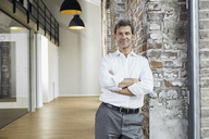 Portrait of confident businessman leaning against brick wall in modern office - PDF01468