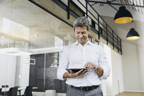 Portrait of mature businessman using tablet in modern office - PDF01471